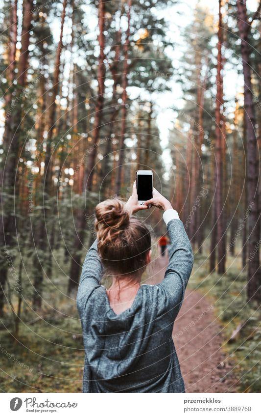 Junge Frau fotografiert mit einem Smartphone während eines Waldspaziergangs in den Sommerferien aktiv Aktivität Ausflugsziel genießen Erkundung Wanderung