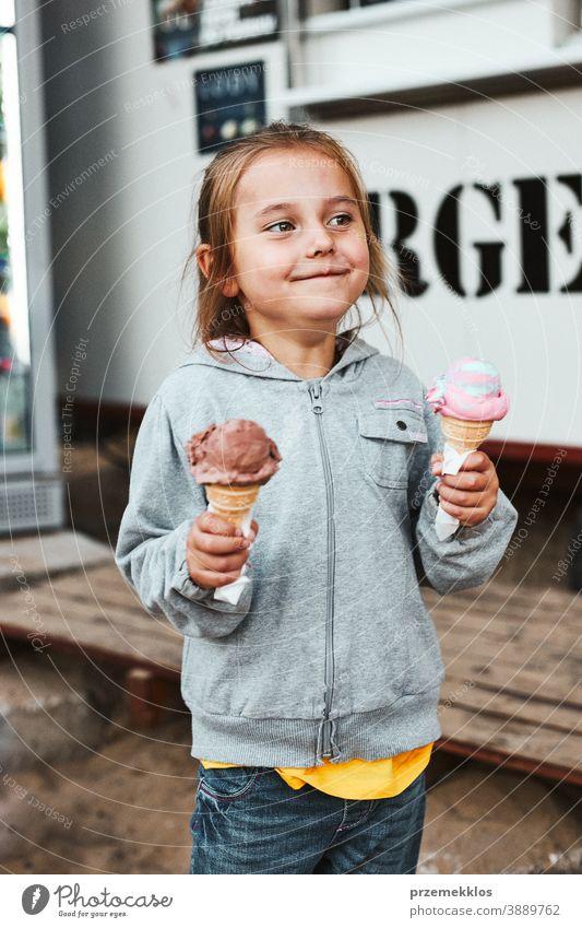Glücklich lächelndes kleines Mädchen hält zwei Eiscreme vor einem Speisewagen Urlaub Familienzeit Familienurlaub Zeit verbringen Ausgaben kaufen Werkstatt Café