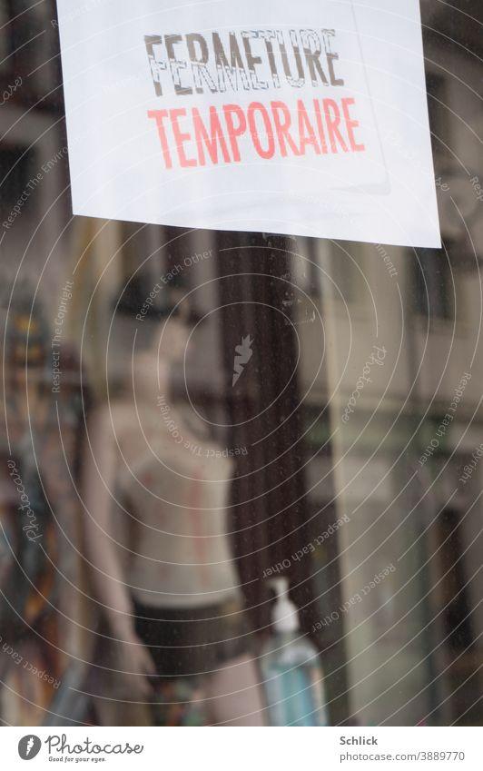 Covid-19 Pandemie Schaufenster eines zeitweise geschlossenen Geschäfts mit Hinweisschild in Französisch Schaufensterpuppe und Flasche mit Handdesinfektionsmittel