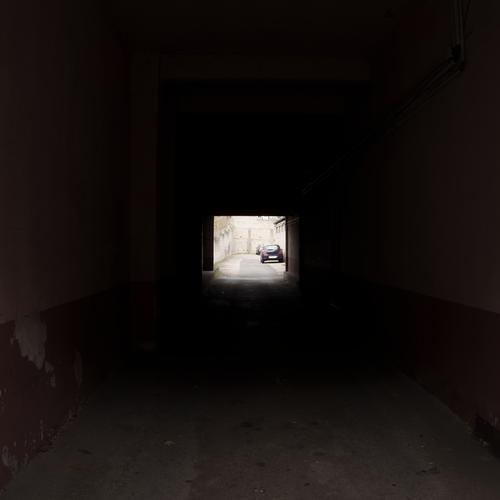 Sehr dunkle quadratische Einfahrt mit im hellen Hintergrund geparkten Autos dunkel parken düster Verbrechen Mord Vergewaltigung Phantasie Schatten