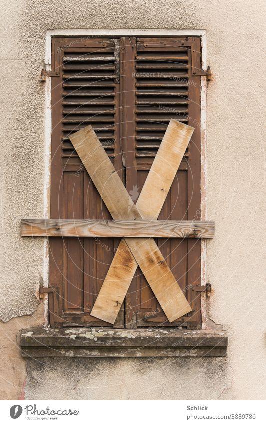 Total zu geschlossener alter Holzklappladen mit Brettern kreuz und quer vernagelt X marode verlassen unbewohnt Fassade Fenster Gebäude Haus Wand Menschenleer