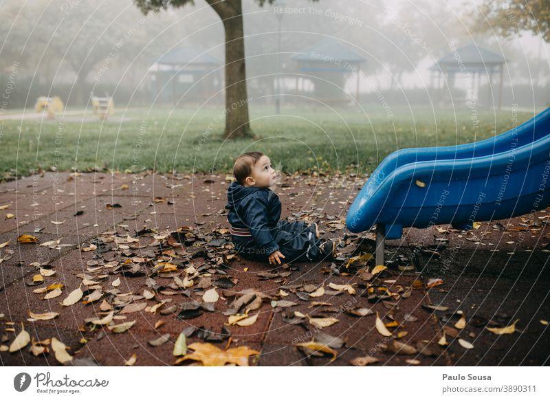 Kleinkind spielt auf dem Spielplatz Herbst authentisch Winter fallen Spielen Sliden Park Kindergarten Außenaufnahme Freude Farbfoto Tag Kindheit