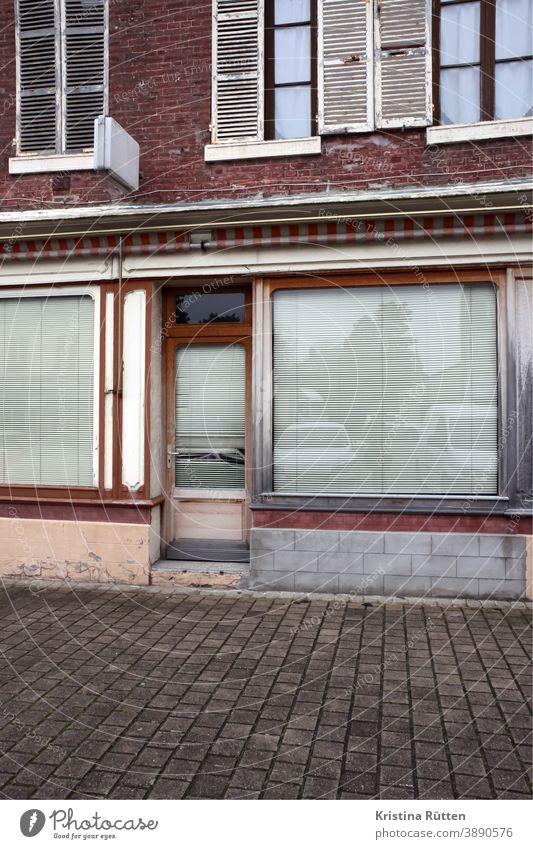 aufgegebenes geschäft geschlossen verlassen schaufenster fassade zu architektur rollos jalousie sichtschutz laden ladenlokal gebäude einzelhandel tür eingang