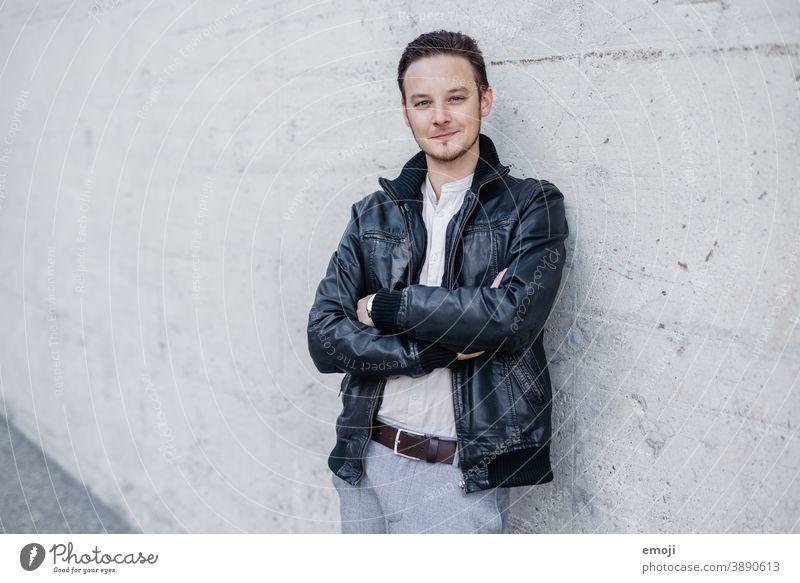 junger Mann in Lederjacke, Business, draussen vor Betonwand männlich Erwachsener Oberkörper die Arme verschränkt Junger Mann Freundlichkeit Lächeln positiv