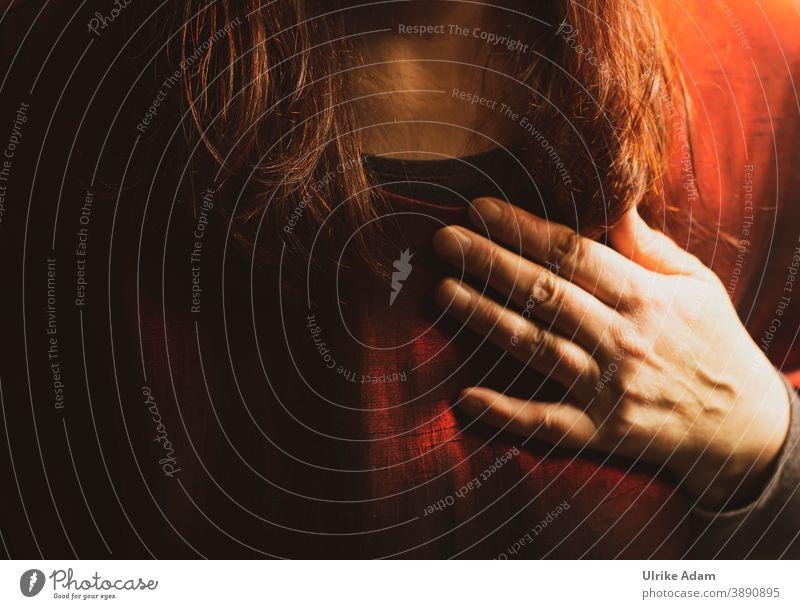 Hand aufs Herz - Frau mit langen roten Haaren hält ihre Hand aufs Herz....die warmen roten Farben der Kleidung untermalen den Schwur der Geste Rot Warm