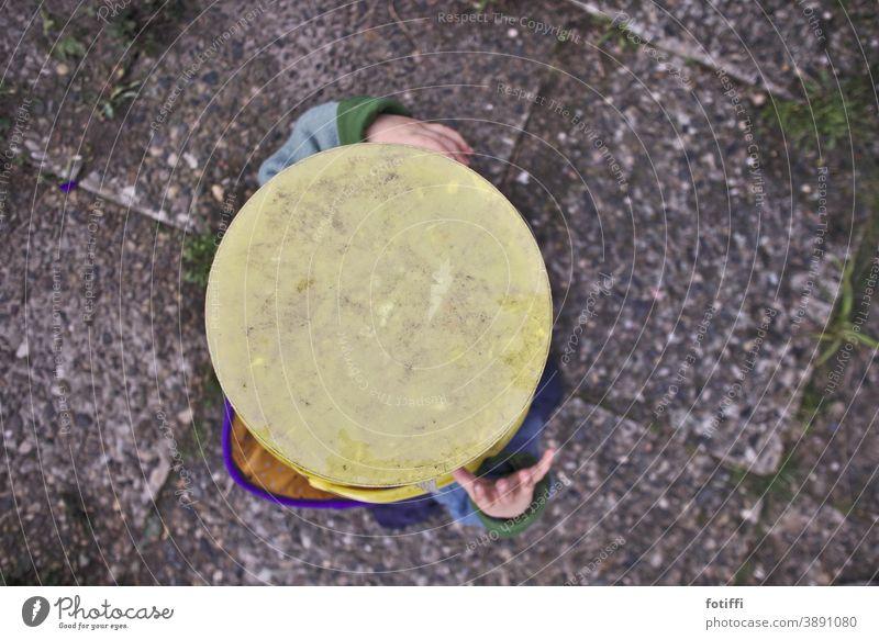 Den Kopf in den Eimer stecken Kind Kleinkind verstecken verstecken spielen Spielen Freude Kindheit 1-3 Jahre Fröhlichkeit von oben waschbeton gelb vergnügt
