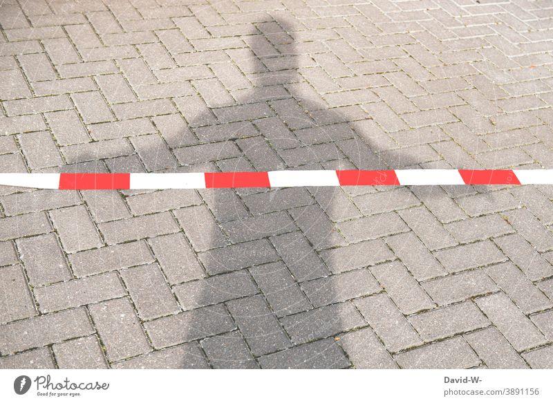 abgesperrt - Schatten eines Mannes hinterm Absperrband silouette verbot Person flatterband Absperrung isolation