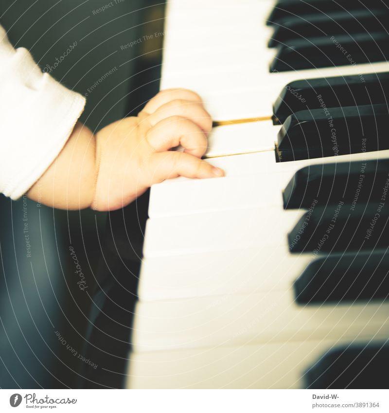 Kind haut in die Tasten Klavier Musik Musikinstrument Baby Kleinkind Kultur musizieren Erziehung Kindererziehung Wohlstand kultiviert Familie Luxus Hand