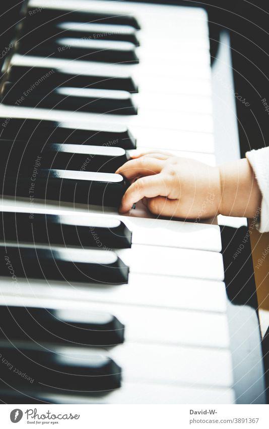 die Hand eines Kindes auf dem Klavier Kleinkind Musik Musikinstrument Kindererziehung Klavier spielen Neugier musizieren niedlich
