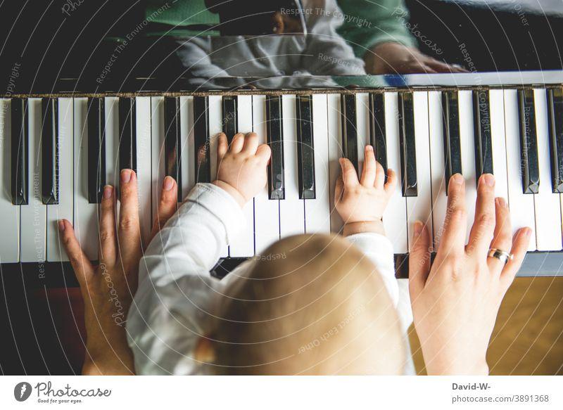 Mutter und Kind machen zusammen Musik musizieren Musikinstrument musikalische früherziehung Kindererziehung Familie Spielen Klavier Hände gemeinsam Kultur