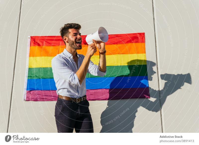 Schwuler Mann schreit in Megaphon auf Straße Lautsprecher schreien Homosexualität lgbt Fahne Regenbogen schwul expressiv männlich lgbtq Stolz Toleranz heiter