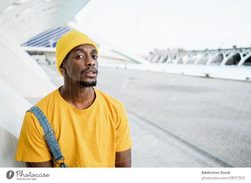 Schwarzer Mann steht auf der Straße und schaut in die Kamera trendy männlich ethnisch schwarz Afroamerikaner gelb Outfit Stil modern hell Vorschein