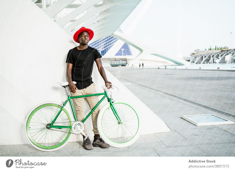 Stilvoller schwarzer Mann mit Fahrrad in der Stadt urban Großstadt jung modern trendy selbstbewusst männlich ethnisch Afroamerikaner Straße Vorschein Hipster