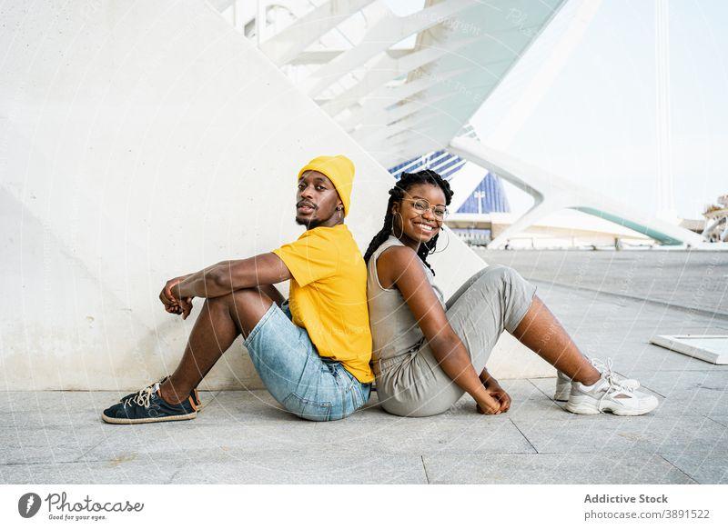 Schwarze Freunde sitzen Rücken an Rücken in der Stadt Zusammensein Straße cool Kurze Haare Vorschein trendy jung urban ethnisch schwarz Afroamerikaner ruhen