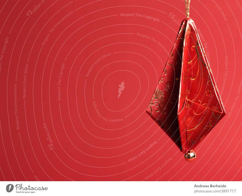 Christbaumschmuck aus schönem rot-goldenen Dekorpapier vor rotem Hintergrund gefaltet Origami Papier Weihnachten selbstgemacht handgefertigt