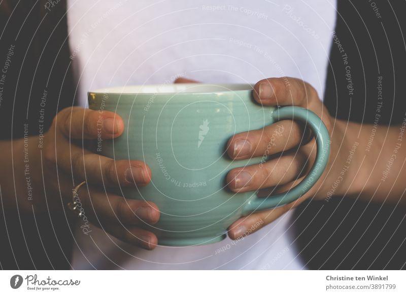 Nahaufnahme einer großen hellgrünen Tasse mit Kaffee oder Tee in den Händen einer jungen Frau. Becher halten festhalten schwarz weiß Getränk Teetasse