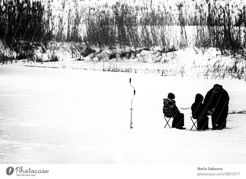 auf einem zugefrorenen Fluss. Kindern beibringen, wie man im Winter Fische fängt. Eisangeln schwarz auf weiß kalt Frost Schnee Baum Lehre Lernen Vater Familie