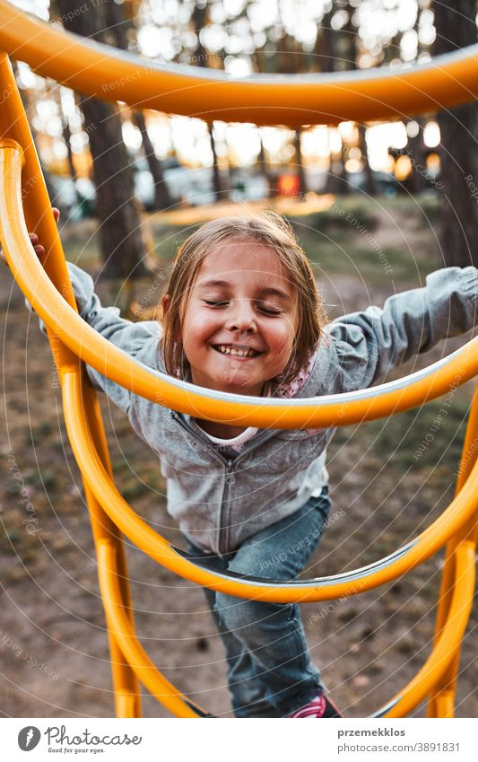Verspieltes glückliches Mädchen im Vorschulalter, das auf einem Spielplatz auf Affenstangen klettert und mit geschlossenen Augen lächelt positiv freudig Junior