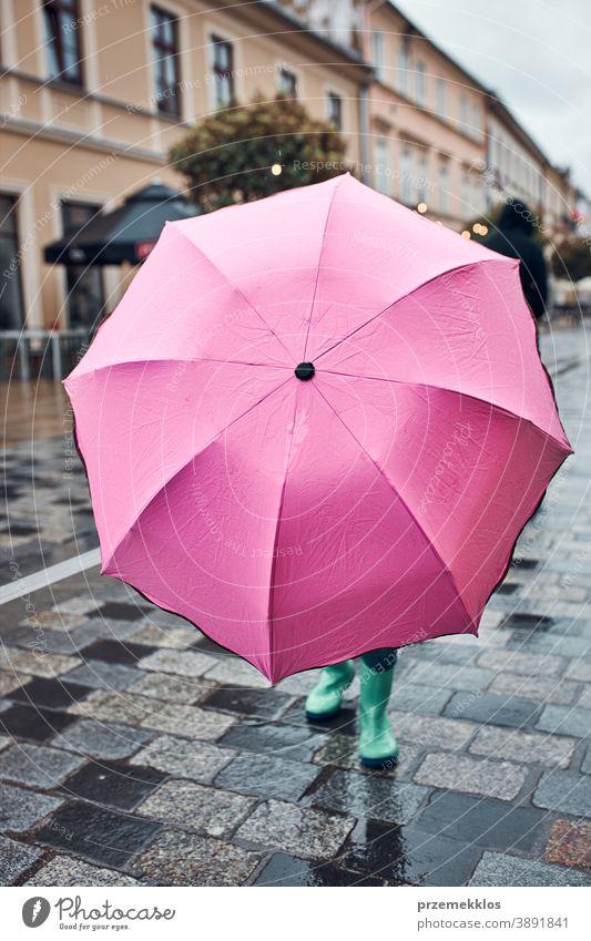 Kind, das sich hinter einem großen rosa Regenschirm versteckt und an einem regnerischen, düsteren Herbsttag in der Innenstadt spazieren geht regnet im Freien