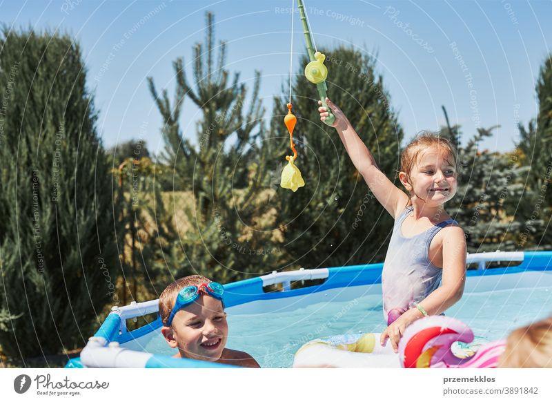 Kinder spielen mit Angelrutenspielzeug in einem Pool im Hausgarten authentisch Hinterhof Kindheit Familie Spaß Garten Fröhlichkeit Glück Freude Lachen Lifestyle
