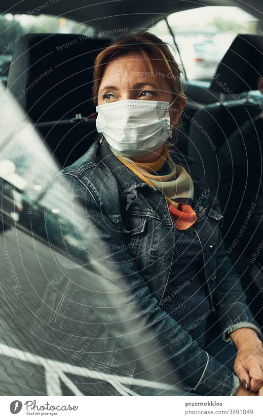 Frau sitzt in einem Auto und trägt die Gesichtsmaske, um eine Virusinfektion zu vermeiden Kaukasier covid-19 Lifestyle Mundschutz Ausbruch Pandemie Schutz