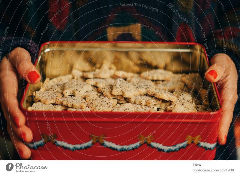 Eine Frau hält eine Plätzchendose mit selbstgebackenen Weihnachtsplätzchen in den Händen Weihnachten Keksdose Tannenbäume Kekse lecker Weihnachten & Advent