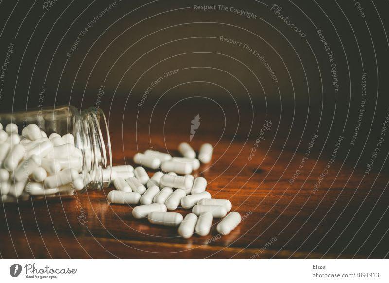 Ein Glas aus dem sich viele weiße Medikamentenkapseln auf einen Tisch ergießen Pillen Medizin Tablette Kapsel Arzneimittel Meidkament Tabletten Vogel Behälter