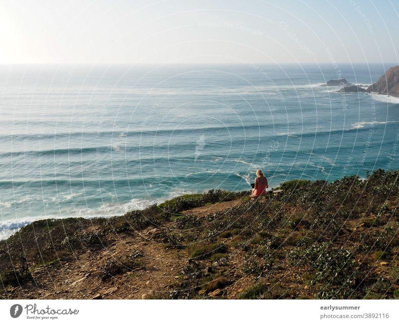 junge Frau, die draußen in der Sonne an ihrem Laptop mit Blick auf das Meer arbeitet Fernarbeit Arbeitsplatz Heimarbeitsplatz Korona-Krise 2020