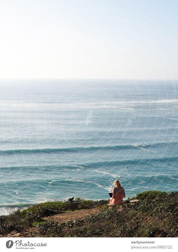 Frau sitzt auf einer Klippe und arbeitet an ihrem Laptop mit Blick auf den Ozean und die Wellen in Portugal Bürofenster Büroarbeit digitaler Nomade Schreibtisch