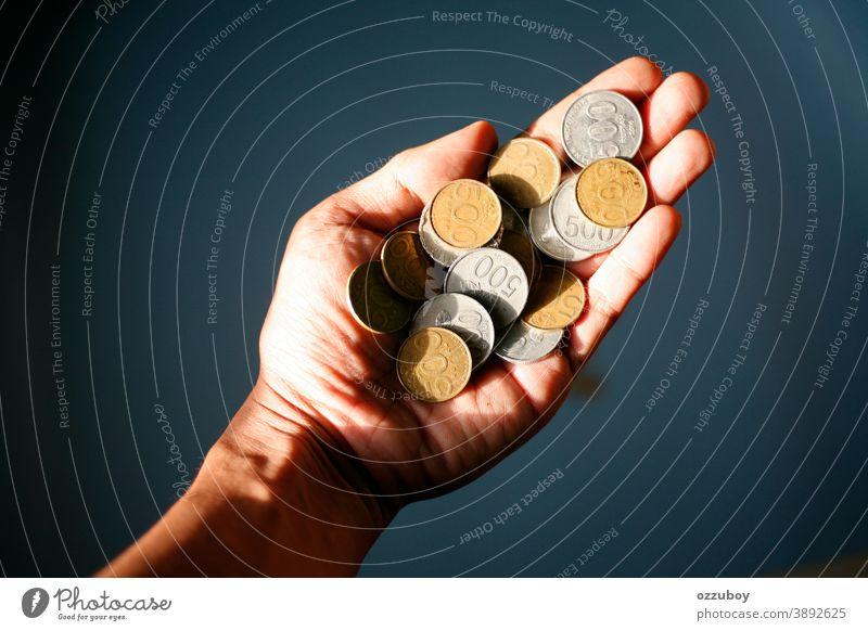 Hand hält 500 Münzen indonesische Rupiah Geldmünzen Beteiligung Kapitalwirtschaft Cent bezahlen sparen Bargeld Wirtschaft Geldinstitut Investition Einsparungen