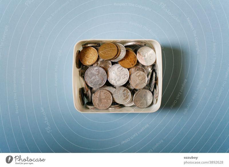 indonesische Rupiah-Münzen auf weißem Kasten Geldmünzen Spardose sparen Farbfoto Kapitalwirtschaft sparsam Geldinstitut Wirtschaft Business Einkommen Bargeld