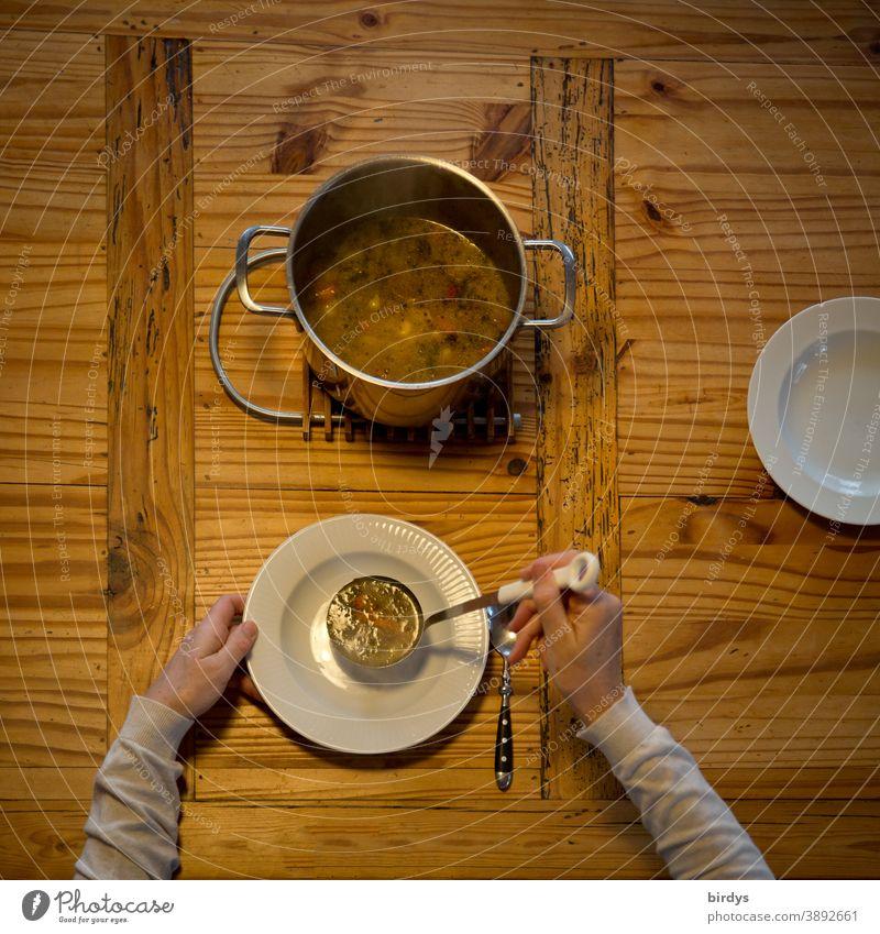 Suppe austeilen, servieren. Gedeckter Holztisch mit Suppentopf, Suppenkelle, Teller und Löffeln. Vogelperspektive Eintopf essen Hände Arme Mittagessen löffeln