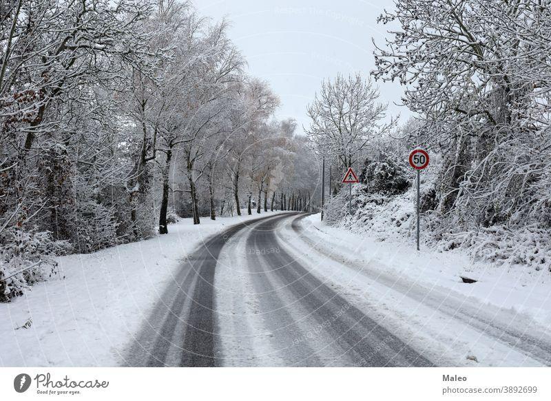 Gefährliche Kurve auf glatter, schneebedeckter Straße im Winter Schnee verschneite gefährlich kalt Wald rutschig reisen drehen. weiß Weg Asphalt Natur