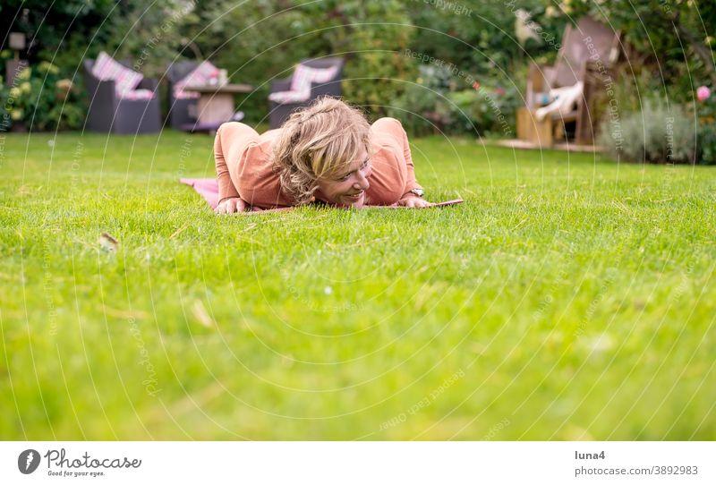 Frau macht Liegestütz im Garten Gymnastik Liegestützen Sport schlapp Kraft Fitness Spaß Muskeln Training Übung lachen fröhlich albern Matte Wiese Rasen