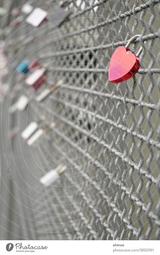 Ein rotes Herzschloss im Vordergrund und weitere Liebesschlösser im Hintergrund sind an einem Brückengeländer befestigt / Liebesbekundung / Ritual Liebesschloss