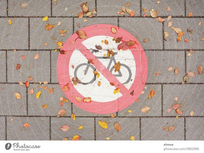 """Auf die graue Betonpflasterstraße aufgemaltes Verkehrszeichen """"Radfahren verboten"""" mit Herbstlaub / Verbotsschild / Verkehrsregelung Schild Verbotszeichen"""