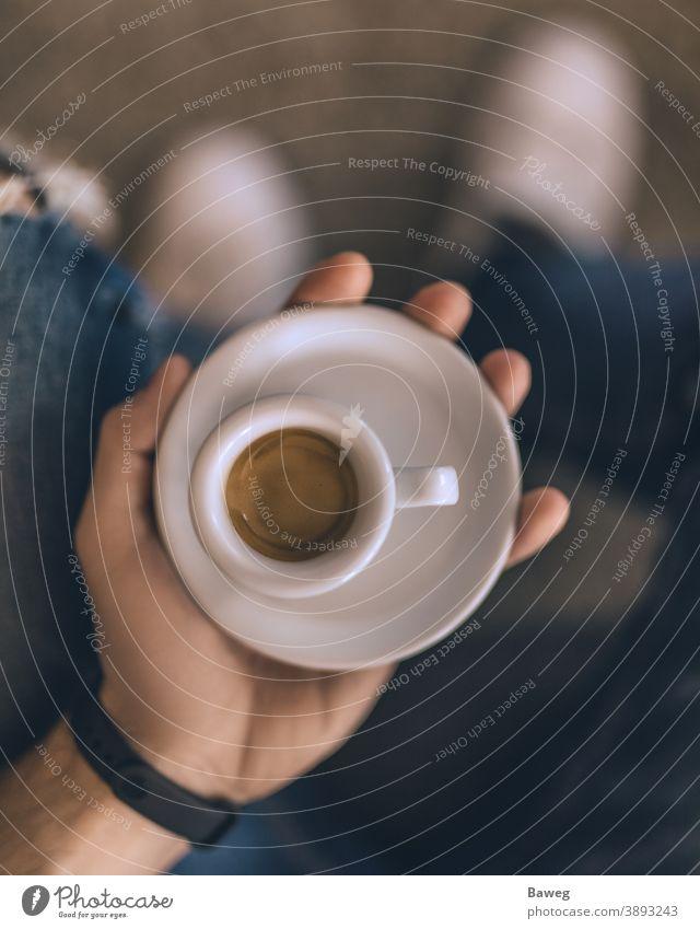 Mann hält Espresso, während er auf der Couch sitzt. zu Hause Körper Frühstück braun Braunton Kälte Kaffee Farben Becher Tiefenschärfe Genießer Genuss Spaß Hand