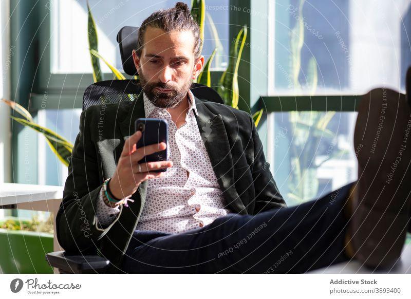 Seriöser Geschäftsmann nutzt Smartphone im Büro benutzend lesen Konzentration ernst Unternehmer Telefon Mobile Pause Mann Vollbart formal Arbeit Arbeitsbereich