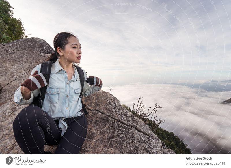 Asiatische Frau sitzt auf einem Felsen in den Bergen Berge u. Gebirge Reisender Cloud Hochland bewundern atemberaubend Wanderer Entdecker genießen asiatisch