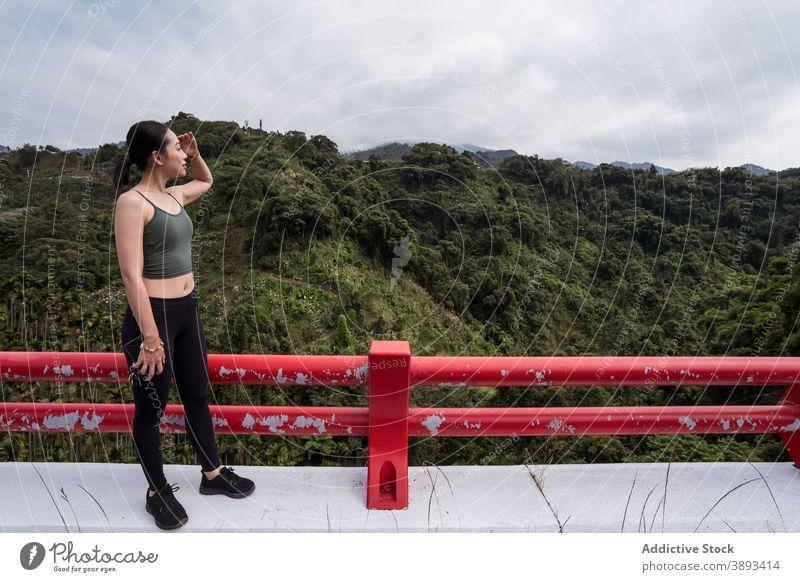 Asiatische Frau genießt die Aussicht auf ein Bergtal Aussichtspunkt Berge u. Gebirge Hochland Reisender bewundern beobachten Tal Sommer erkunden ethnisch