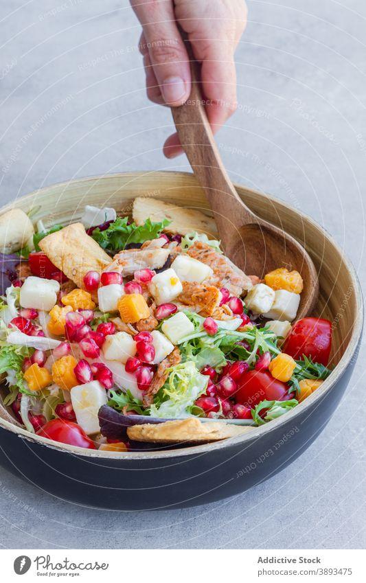 Crop Person serviert leckeren Caesar-Salat Salatbeilage Schalen & Schüsseln festlich Abendessen Käse Granatapfel Hähnchen grün Cracker Samen Bestandteil Koch