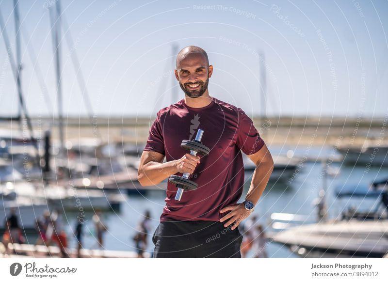 Ein Mann steht mit Gewichten im Freien am Meer Porträt Übung Sport Seeküste Park urban Tag sonnig jung stehen Textfreiraum Jachthafen Boot ernst Trainerin