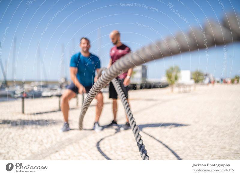 Kampfseile im Freien von Mann und seinem Personal Trainer verwendet Drahtseile Trainerin Übung Seile Schlacht Kreuzpassung Sportler Schwitzen Männer Ausdauer