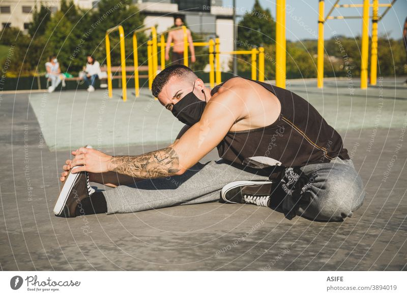Junger Mann mit Gesichtsmaske, der sich vor dem Training der Gymnastik dehnt calisthenics Sport Aufwärmen strecken Athlet Mundschutz Coronavirus neue Normale