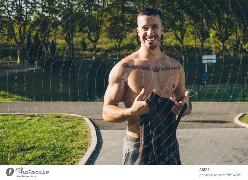Junger städtischer Bodybuilder zieht vor dem Gymnastiktraining das Hemd aus Athlet Mann Muskeln Stärke Kunstturnen Straße Glück lustig Lächeln Porträt Freestyle