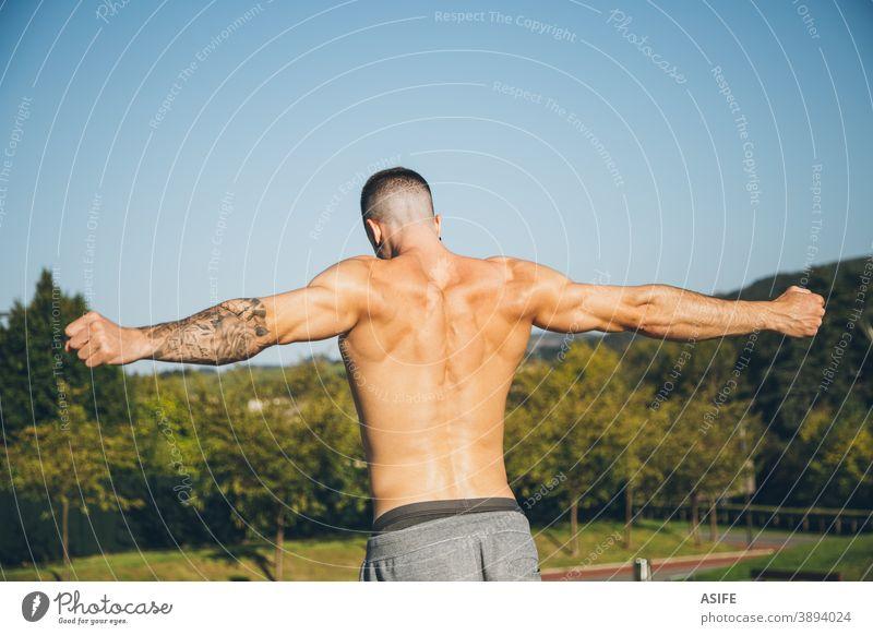 Junger Stadtsportler beim Aufwärmen vor dem Gymnastiktraining calisthenics Sport strecken Athlet Mann Muskeln Rücken Stärke Kunstturnen Straße Freestyle Körper