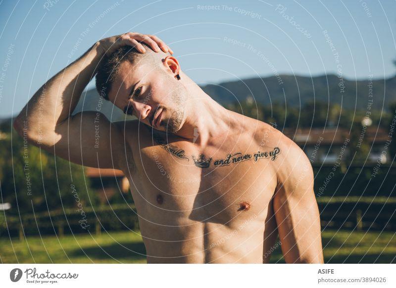 Junger Stadtsportler, der seinen Hals vor dem Training der Gymnastik dehnt calisthenics Sport Aufwärmen strecken Athlet Mann Muskeln Stärke Kunstturnen Straße