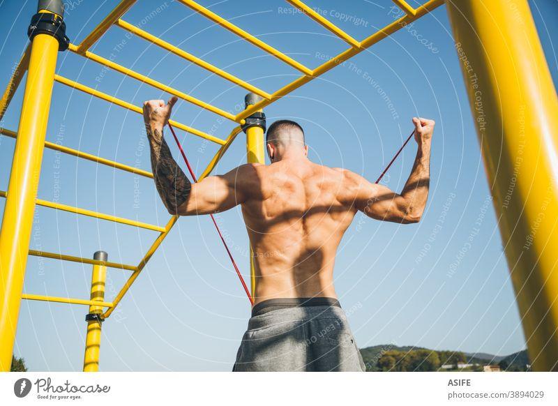Junger Mann dehnt ein Widerstandsgummiband vor dem Training der Gymnastik calisthenics Sport Aufwärmen strecken Gummiband Widerstandsband Athlet Muskeln Stärke