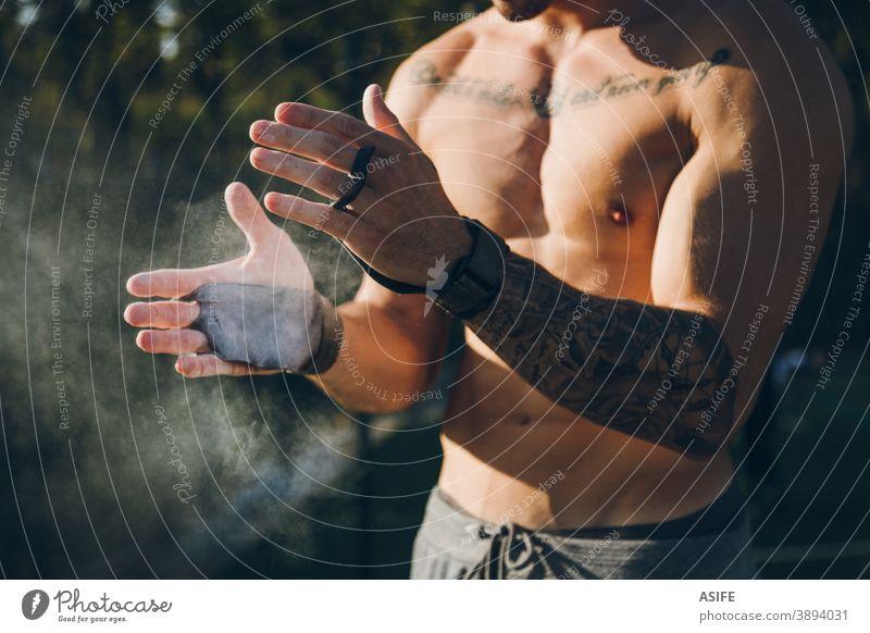Junger Stadtsportler mit Griffen aus dem Fitnessstudio klatscht in die Hände mit Magnesiumkreide für Gymnastik calisthenics Griffe im Fitnessstudio Handschuhe