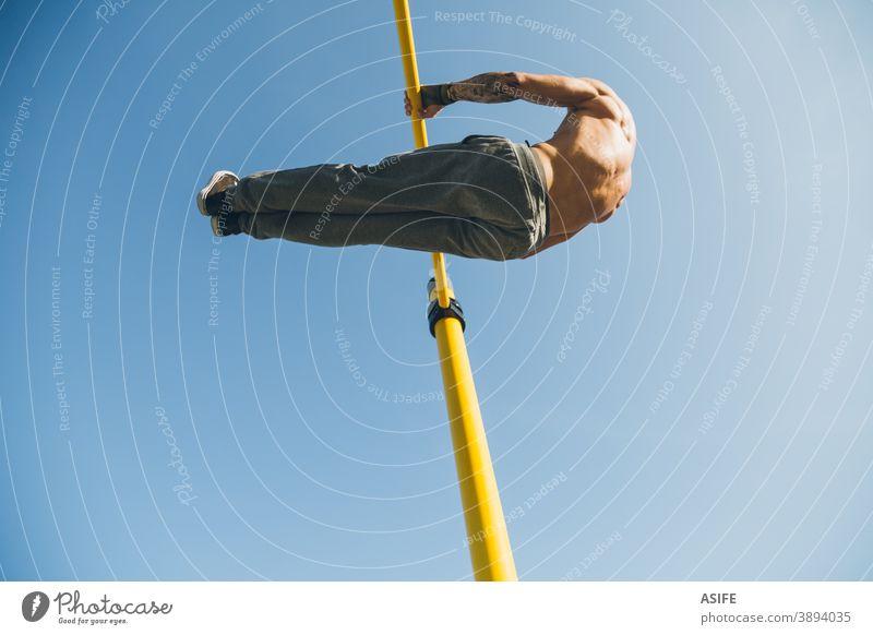 Junger athletischer Mann turnt am Barren in einem Gymnastikpark calisthenics Sport Athlet Muskeln Stärke Kunstturnen Straße Freestyle pirouettieren herumwirbeln